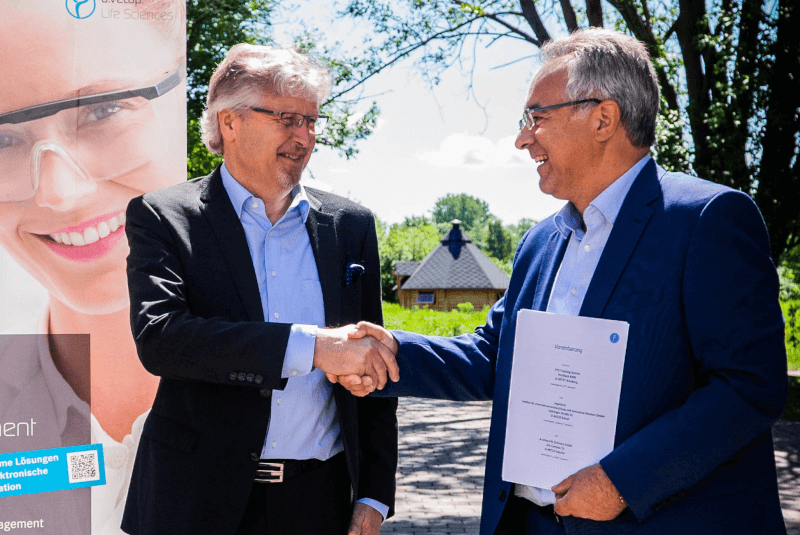 Illustration of the signing of the contract between Mr. Schnettler of PTS and Mr. Gukelberger of d.velop Life Sciences